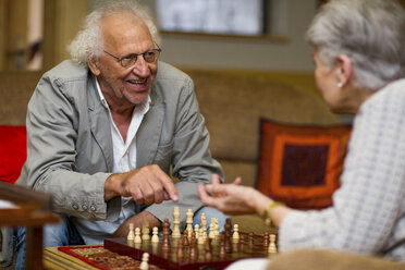 Senior man and woman playing chess in retirement home - ZEF14211