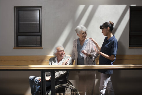 Gereatric nurse helping senior man and woman to walk down corridor - ZEF14220