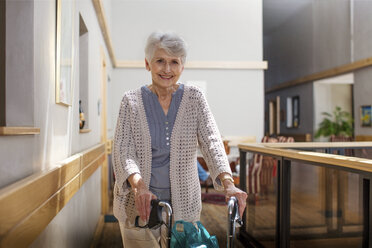 Senior woman in retirement home pushing wheeled walker - ZEF14226