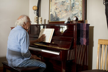 Senior man playing piano at retirement home - ZEF14238