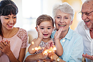 Little girl lwatching sparklers on a birthday cake, sitting on grandmother's lap - ZEF14250