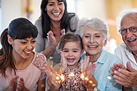 Little girl lwatching sparklers on a birthday cake, sitting on grandmother's lap, with family around - ZEF14253