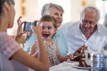 Grandparents celebrating a birthday with their granddaughter, taking picture with smartphone - ZEF14259