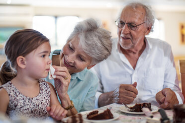 Grandparents celebrating a birthday with their granddaughter, eating chocolate cake - ZEF14262