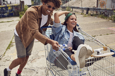 Young man pushing girlfriend sitting in shopping cart - SUF00247