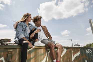Young couple sitting on a wall - SUF00253