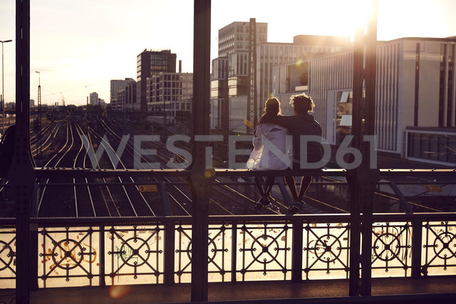 Germany, Munich, Young couple sitting on bridge, enjoying sunset - SUF00262 - Sullivan/Westend61