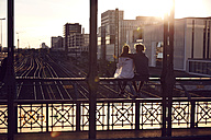 Germany, Munich, Young couple sitting on bridge, enjoying sunset - SUF00262