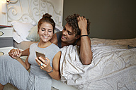 Young couple sitting on bed, talking, using smartphone - SUF00271