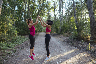 Two active women high fiving in forest - JPF00258
