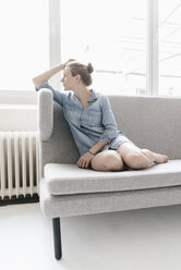 Woman sitting on couch in a loft looking out of window - KNSF02242