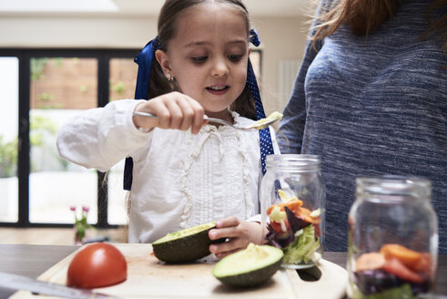 Portrait of little girl preparing healthy salad with her mother in the kitchen - IGGF00003