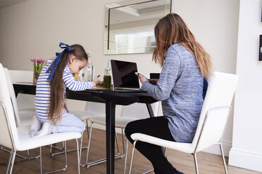 Little girl drawing at table while her mother using cell phone - IGGF00009