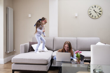 Little girl wearing sunglasses jumping on sofa while her mother working on laptop at coffee table - IGGF00018