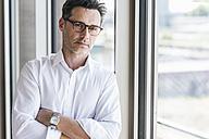 Portrait of sceptical businessman standing in front of window - UUF11217
