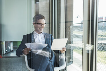 Smiling businessman with documents looking at tablet - UUF11223