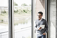 Pensive businessman with tablet looking through window - UUF11244