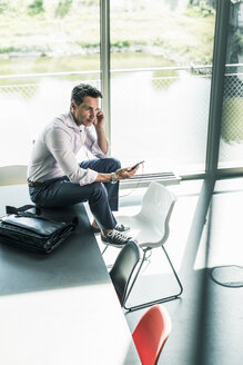 Businessman in office sitting on desk, using smartphone - UUF11259