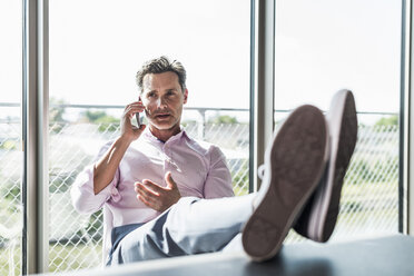 Businessman sitting at desk with feet up, using smartphone - UUF11283