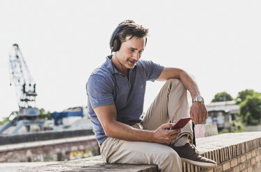 Businessman sitting on a wall, using smartphone and headphones - UUF11289