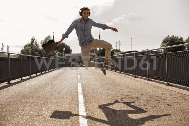 Businessman with headphones and briefcase jumping for joy on a road - UUF11292