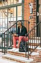 USA, NYC, Brooklyn, Man waiting on stairs, using smartphone - JUBF00225