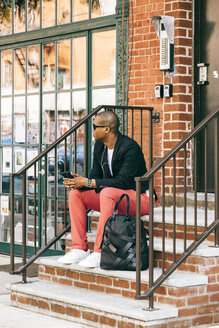 USA, NYC, Brooklyn, Man waiting on stairs, using smartphone - JUBF00225