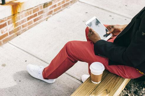 Man sitting in the street, using digital tablet, drinking coffee - JUBF00231