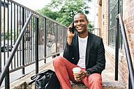 USA, NYC, Brooklyn, Man waiting on stairs, using smartphone - JUBF00234