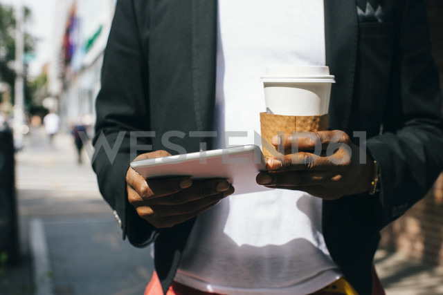USA, NYC, Brooklyn, Man walking in the street, holding cup of coffee and digital tablet - JUBF00237