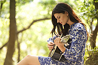 Young woman playing guitar in forest - MFRF00937