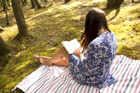 Young woman sitting on blanket in forest reading a book - MFRF00940