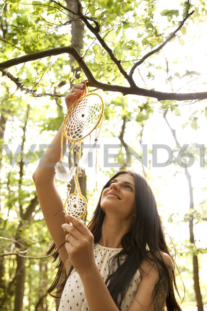 Woman hanging dream catcher on branch of a tree - MFRF00943