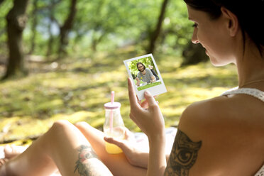 Young woman sitting on blanket in forest looking at instant photo - MFRF00946