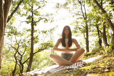 Young woman sitting on blanket in forest practicing yoga - MFRF00949