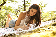 Young woman lying on blanket in forest writing a letter - MFRF00952