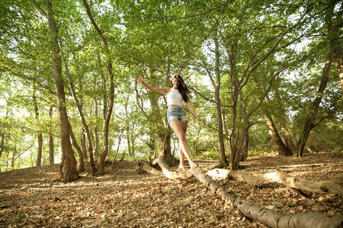 Young woman in forest balancing on a log - MFRF00955