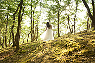 Rear view of young woman in forest wearing tulle skirt - MFRF00958