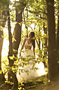 Young woman in forest wearing tulle skirt and bra - MFRF00961