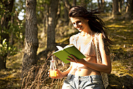 Young woman in forest reading a book - MFRF00964