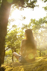 Young woman sitting in forest at sunset - MFRF00970
