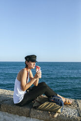Young woman drinking smoothie at the sea - KIJF01672