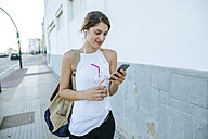 Young woman with cell phone and smoothie walking down the street - KIJF01675