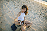 Young woman taking a selfie with a smartphone on the beach - KIJF01687