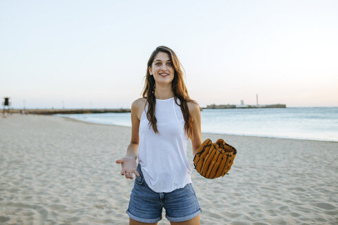 Young woman playing with baseball glove on the beach at sunset - KIJF01690