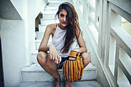 Young woman sitting on steps with ball and baseball glove - KIJF01693