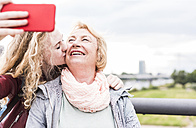 Grandmother and granddaughter taking selfie with smartphone - UUF11352