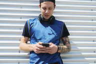 Tattooed young man with headphones looking at cell phone - FMOF00289