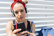 Portrait of young woman with headphones looking at smartphone - FMOF00298