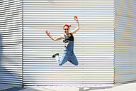 Smiling young woman jumping in the air - FMOF00301